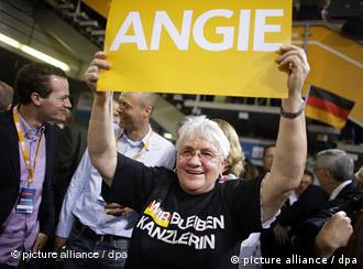 Supporter of Angela Merkel holding a poster which reads Angie