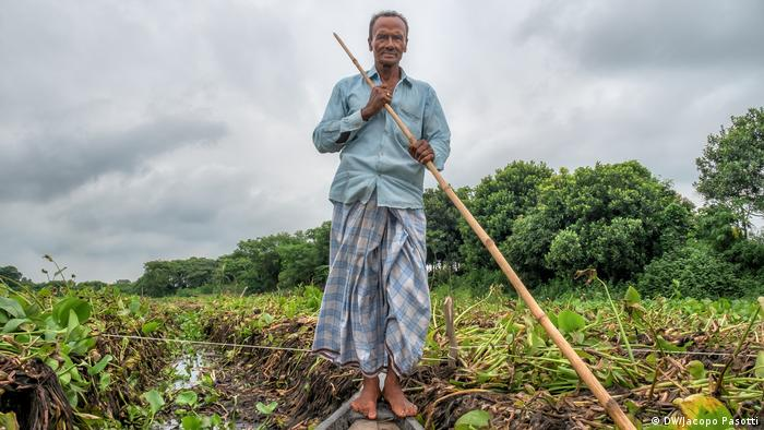 A man navigates between crops floating atop the water