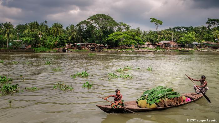 Boys row to market in Pirojpun, Bangladesh, after heavy rainfall