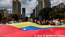 Opposition demonstrators display a Venezuelan national flag during a protest against the government of President Nicolas Maduro, called by opposition leader and self-proclaimed acting president Juan Guaido, at Altamira square in Caracas on January 30, 2019. - Venezuelan President Nicolas Maduro hit out Wednesday at military mercenaries he says are conspiring to divide the armed forces and plot a coup as the opposition planned a new protest to force the socialist leader from power. (Photo by Yuri CORTEZ / AFP) (Photo credit should read YURI CORTEZ/AFP/Getty Images)