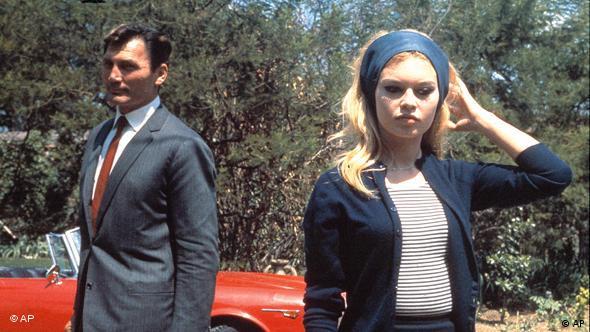 Brigitte Bardot und Jack Palance vor rotem Sportwagen in Die Verachtung (AP Photo)