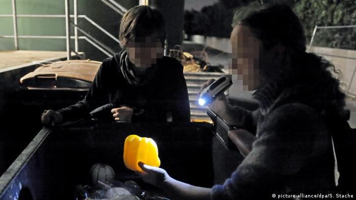 Две девушки достают перец из мусорного контейнера вблизи супермаркета