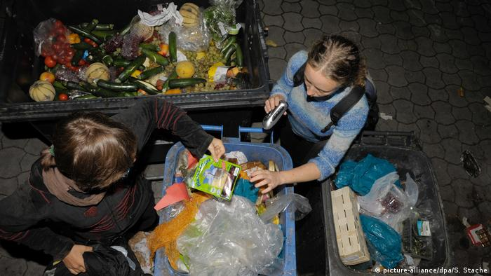 Dumpster diving: young women salvage food from dumpster at night