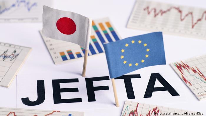EU-Japan free trade deal symbolized by miniature EU and Japanese flags surrounded by bar charts and graphs
