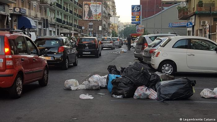 A street full of cars. The street is strewn with rubbish