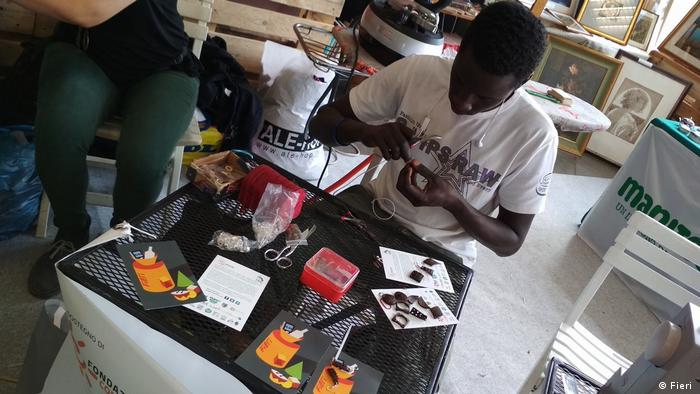A man sits a table with scissors and other items to make crafts