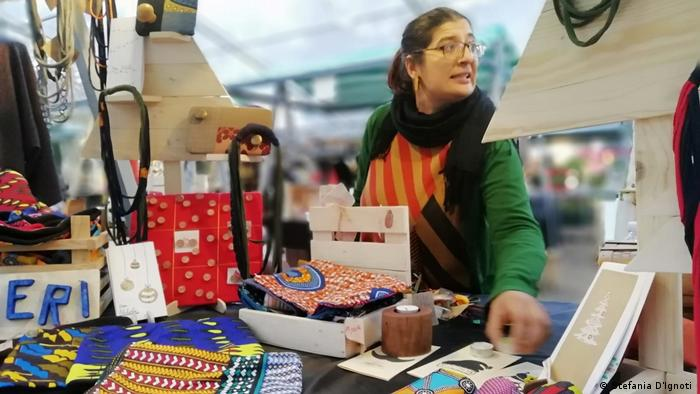 A woman at a market stall full of goods made of recycled materials