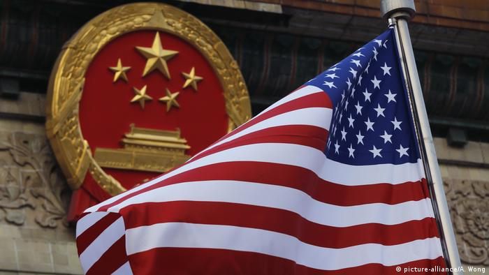 An American flag is flown next to the Chinese national emblem in Beijing