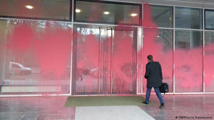 Man walks towards the defaced entrance of the Brazil embassy in Berlin
