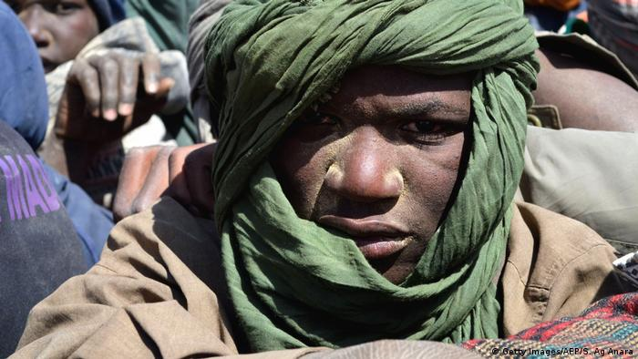 A young African man, his head wrapped in a scarf, looks out from a truck full of migrants