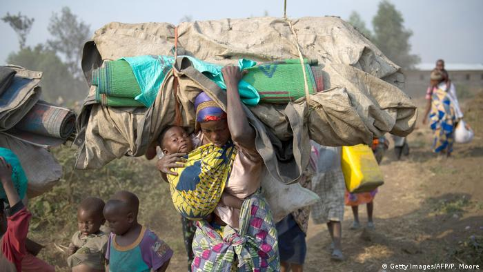 A woman carrying a child and her belongings on the move in DRC