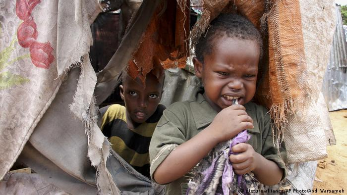 A young boy stands at the entrance to a makeshift shelter in the Daryeel refugee camp in Kenya, looking upset. Another young boy looks out from inside the shelter.