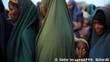 A young Somali girl who fled violence and drought in Somalia stands in line among adults outside a food distribution point in Dadaab refugee camp in northeastern Kenya on July 5, 2011. Dadaab, a complex of three settlements, is the world's largest refugee camp. Built to house 90,000 people and home to more than four times that number, it was already well over its maximum capacity before an influx of 30,000 refugees in the month of June. Upon arrival, the refugees find themselves tackling a chaotic system that sees new arrivals go days, even weeks, without food aid. It still takes too much time for refugees to get proper assistance, Antoine Froidevaux, MSF's field coordinator in Dadaab told AFP. The answer in terms of humanitarian aid is not satisfactory at all at the moment. AFP PHOTO/Roberto SCHMIDT (Photo credit should read ROBERTO SCHMIDT/AFP/Getty Images)