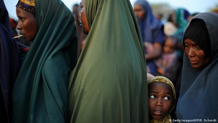 Women and a girl in hijab huddle in a queue at the Dadaab refugee camp in Kenya.