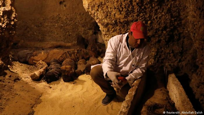 An archaeologist sits next to a mummy inside a tomb
