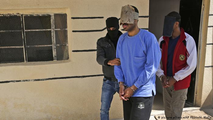 IS fighters Alexanda Kotey and El Shafee Elsheikh escorted by a Kurdish security officer