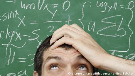 Ein Mann hält sich den Kopf und blickt auf eine Schultafel voller mathematischer Formeln