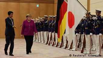 Chancellor Angela Merkel and Japanese Prime Minister Shinzo Abe walk past honour guards at Abe's official residence.