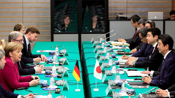 German Chancellor Angela Merkel speaks to Japanese Prime Minister Shinzo Abe at the start of their meeting at Abe's official residence in Tokyo