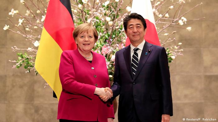 German Chancellor Angela Merkel (L) is welcomed by Japanese Prime Minister Shinzo Abe