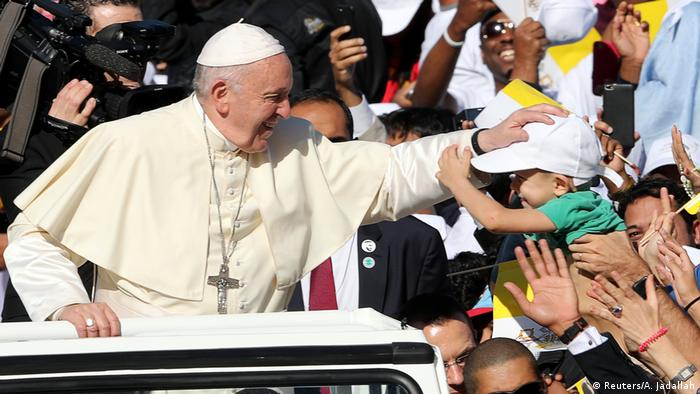 Pope Francis touches a baby's head as he is greeted by cheering crowds