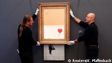Employees of the Frieder Burda museum put Banksy's partially shredded artwork Love is in the bin in place at the museum in Baden Baden, Germany, February 4, 2019. REUTERS/Kai Pfaffenbach