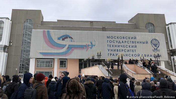 Students gather outside after being evacuated from Moscow State Technical University of Civil Aviation due to a fake bomb threat