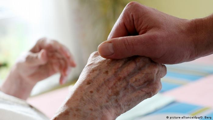 A person holds an elderly woman's hand in a nursing home