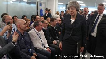 Theresa May walks by a bunch of reporters as she prepares to give a speech on Brexit
