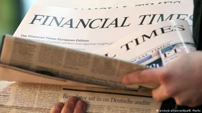 Человек берет в руки газету Financial Times