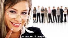 junge attraktive Geschaeftsfrau mit Brille steht vor ihrem Team und laechelt   young attractive businesswoman with glasses,standing in front of her team, smiling   Verwendung weltweit