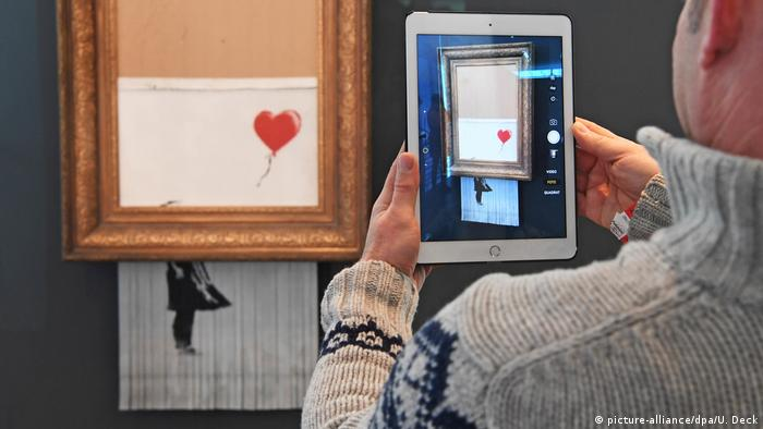 Half-shredded Girl with Balloon in museum, with someone holding an IPad in front of it (picture-alliance/dpa/U. Deck)