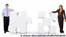 zwei Geschaeftsleute lehnen an ueberdimensionalen Puzzle-Teilen | young business persons leaning against giant puzzle pieces | Verwendung weltweit