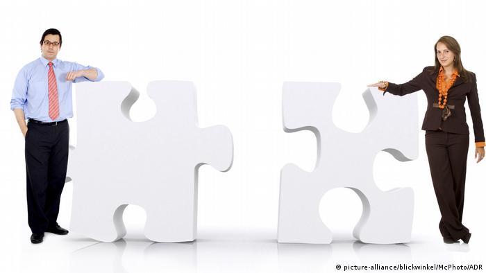 Zwei Geschäftsleute lehnen an überdimensionalen Puzzle-Teilen