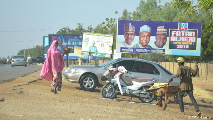 Nigerians walk past election posters (DW/K. Gänsler)