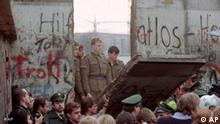 ** FILE ** East German border guards look through a hole in the Berlin wall after demonstrators pulled down one segment of the wall at Brandenburg gate in this November 11, 1989 file picture. Thursday, Nov. 9, 2006 marks the 17th anniversary of the fall of the Berlin Wall. (AP Photo/Lionel Cironneau, File)
