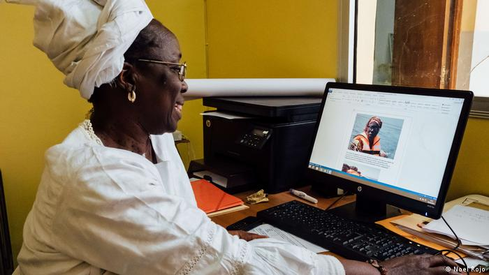 Senegal: Woman sits in front of a computer and reads an online article