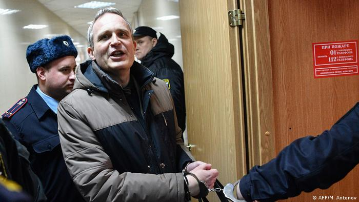 Dennis Christensen, a Danish Jehovah's Witness accused of extremism, is escorted into a courtroom to hear his verdict