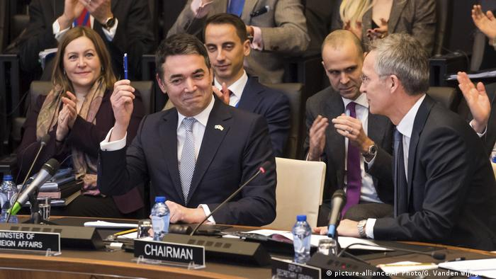 NATO Secretary General Jens Stoltenberg looks at Macedonia's Foreign Minister Nikola Dimitrov as he holds a pen during the signing of the accession protocol in a ceremony at NATO headquarters in Brussels.