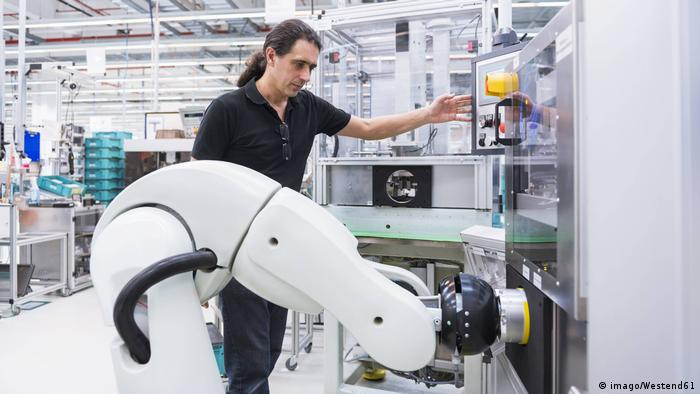 A man works with an assembly robot in a factory
