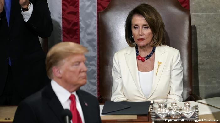 Nancy looks off into the distance while sitting in Congress as a blurry Trump stands before her