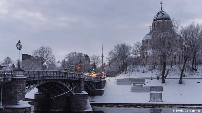 A church stands next to a bridge in Vilnius. The TV tower is seen in the distance
