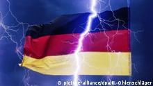 Ein Blitz scheint eine deutsche Flagge in zwei Teile zu spalten. | Verwendung weltweit