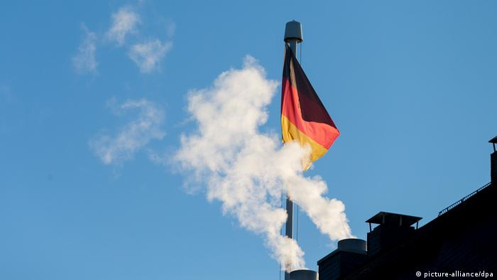 A German flag flies as emissions come out of a chimney (picture-alliance/dpa)