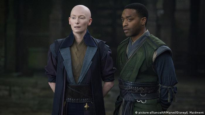 Tida Swinton, bald and dressed in black, plays Ancient One. She stands next to another character from the film (picture-alliance/AP/Marvel/Disney/J. Maidment)