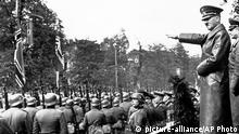 German Chancellor Adolf Hitler salutes units of the German army, in Warsaw, Poland, Oct. 5, 1939. At far right is General Von Brauchitsch, Chief of the German Army. (AP Photo) |