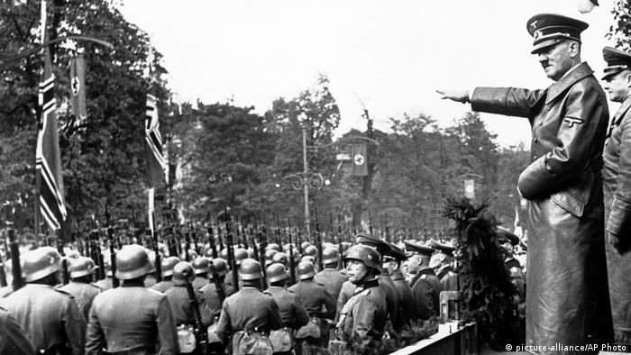 Adolf Hitler nimmt mit gestreckten Arm eine Parade ab (picture-alliance/AP Photo)