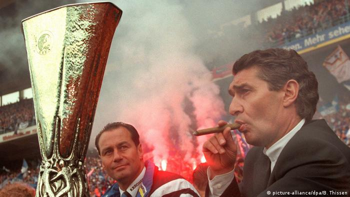 Am Tag nach dem Gewinn des UEFA-Cups 1997 hält der damalige Schalke-Manager Rudi Assauer (r.) im Gelsenkirchener Parkstadion, neben dem damaligen Trainer Huub Stevens (l.) sitzend, vor begeistertem Publikum den Pokal (Foto: picture-alliance/dpa/B. Thissen)