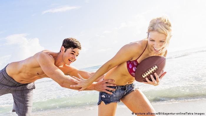 Paar spielt am Strand mit Football (picture-alliance/Bildagentur-online/Tetra Images)
