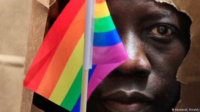 A man holds a small rainbow flag in front of his face